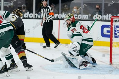 Vegas Golden Knights center Cody Glass (9) scores on Minnesota Wild goaltender Cam Talbot (33) during the second period of an NHL hockey game, in Las Vegas