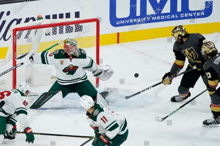 Vegas Golden Knights right wing Alex Tuch (89) scores on Minnesota Wild goaltender Cam Talbot (33) to tie the game in the final minute of the third period of an NHL hockey game, in Las Vegas