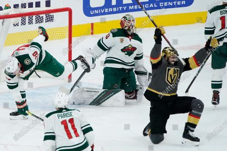 Vegas Golden Knights right wing Alex Tuch, right, celebrates after scoring against Minnesota Wild goaltender Cam Talbot (33) to tie the game in the final minute of the third period of an NHL hockey game, in Las Vegas