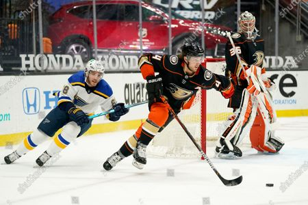 Anaheim Ducks defenseman Cam Fowler, center, moves the puck as St. Louis Blues left wing Mike Hoffman, left, chases and goaltender John Gibson watches during the first period of an NHL hockey game, in Anaheim, Calif