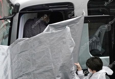 Seen behind plastic sheets, a man believed to be Peter Taylor (top) enters a bus upon his arrival at Narita airport, near Tokyo, Japan, 02 March 2021.Michael Taylor and his son Peter Taylor are suspected to have helped former Nissan Motor Co. Chairman Carlos Ghosn in his escape from Japan in 2019.