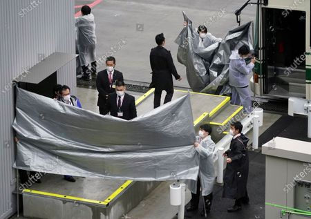 Police officers set up plastic sheets to block the view before the arrival of Michael Taylor and his son Peter Taylor at Narita airport, near Tokyo, Japan, 02 March 2021. Michael Taylor and his son Peter Taylor are suspected to have helped former Nissan Motor Co. Chairman Carlos Ghosn in his escape from Japan in 2019.