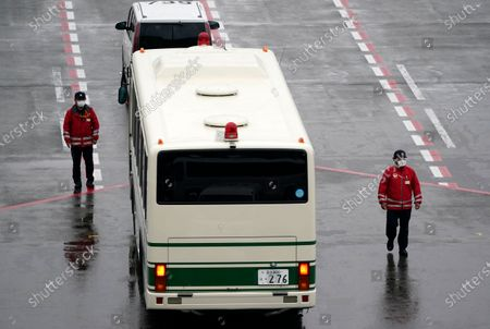 Stock Image of Ground personnel walk past a bus believed to be carrying Michael Taylor after his arrival at Narita airport, near Tokyo, Japan, 02 March 2021. Michael Taylor and his son Peter Taylor are suspected to have helped former Nissan Motor Co. Chairman Carlos Ghosn in his escape from Japan in 2019.