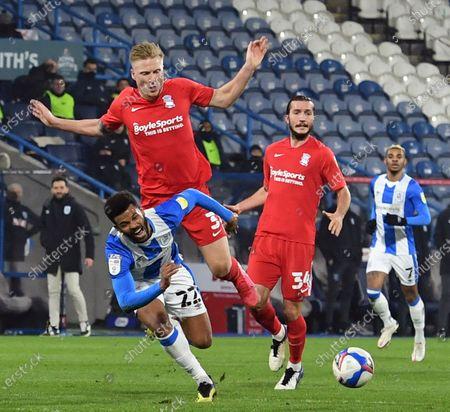 Birmingham City's Kristian Pedersen fouls Huddersfield's Fraizer Campbell