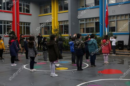 Pupils of a primary school, reopened for face-to-face education along with some others in several regions across Turkey, sing the national anthem as they gather for the first time following lockdown in Istanbul, . The easing of coronavirus restrictions were announced by Turkish President Recep Tayyip Erdogan late Monday following a cabinet meeting, even as infections spiked to the highest level since mid-January