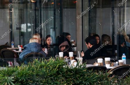 People sit on a coffee shop reopened for business as cafes, restaurants and other eateries reopened in some provinces across Turkey, in Istanbul, . The businesses are allowed to operate at half-capacity between the hours of 7:00 a.m. and 07:00 p.m. as coronavirus restrictions are eased, although infections have spiked in recent days to the highest level since mid-January