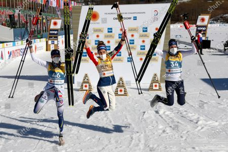 Winner Therese Johaug of Norway, center, celebrates flanked by second placed Frida Karlsson of Sweden, left, and third placed Ebba Andersson of Sweden after the 10km women's interval start free race at the FIS Nordic World Ski Championships in Oberstdorf, Germany, Tuesady