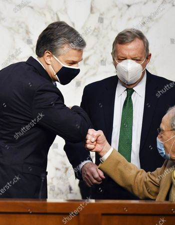 Director Christopher Wray, left, greets Ranking Member Chuck Grassley, R-Iowa, as Sen. Dick Durbin, D-Ill., looks on as he arrives to testify before the Senate Judiciary Committee on Capitol Hill in Washington