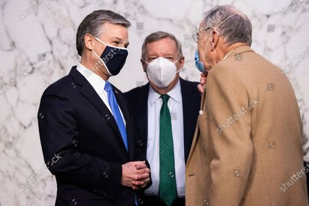 Director Christopher Wray, left, greets Sen. Chuck Grassley, R-Iowa, right and Sen. Dick Durbin, D-Ill., as he arrives to testify before the Senate Judiciary Committee on Capitol Hill in Washington