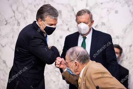 Director Christopher Wray, left, greets Sen. Chuck Grassley, R-Iowa, right as Sen. Dick Durbin, D-Ill., looks on before the Senate Judiciary Committee on Capitol Hill in Washington