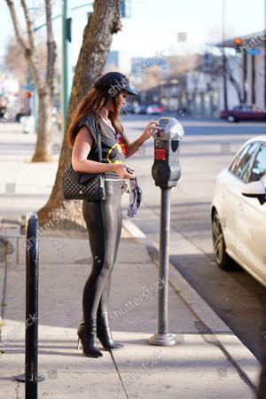 Danielle Vasinova goes to put money in the parking meter.