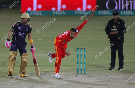 Stock Photo of Islamabad United's Faheem Ashraf, center, delivers a ball while Quetta Gladiators' Faf du Plessis watches, during a Pakistan Super League T20 cricket match between Islamabad United and Quetta Gladiators at the National Stadium, in Karachi, Pakistan