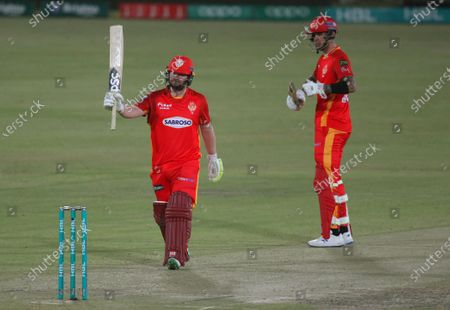 Islamabad United' Paul Stirling, left, raises bat to celebrate after scoring fifty while teammate Alex Hales watches duirng a Pakistan Super League T20 cricket match between Islamabad United and Quetta Gladiators at the National Stadium, in Karachi, Pakistan