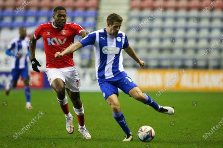 Stock Photo of Wigan Athletic defender Scott Wootton (14) and Charlton Athletic midfielder Chuks Aneke (10) during the EFL Sky Bet League 1 match between Wigan Athletic and Charlton Athletic at the DW Stadium, Wigan