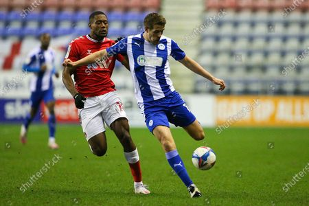 Stock Picture of Wigan Athletic defender Scott Wootton (14) and Charlton Athletic midfielder Chuks Aneke (10) during the EFL Sky Bet League 1 match between Wigan Athletic and Charlton Athletic at the DW Stadium, Wigan