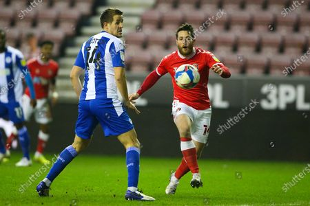 Charlton Athletic forward Conor Washington (14) and Wigan Athletic defender Scott Wootton (14) the EFL Sky Bet League 1 match between Wigan Athletic and Charlton Athletic at the DW Stadium, Wigan