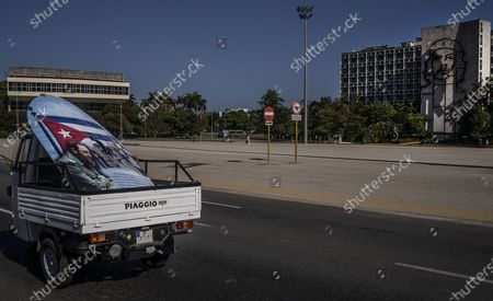 Pickup truck, hauling a poster of Fidel Castro, drives past Revolution Square completely empty of tourists, in Havana, Cuba, . The Caribbean is hunting for visitors and vaccines to jump-start the stalled economy in one of the world's most tourism-dependent regions