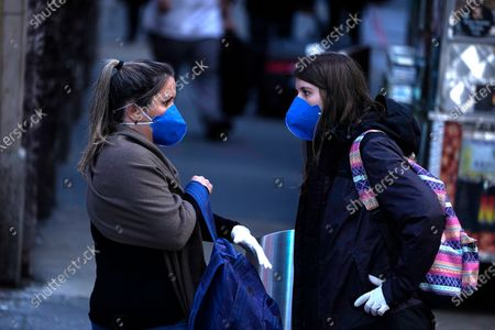 Stock Image of Women wearing a protective mask walk around the Broadway Theatre that Broadway productions have been suspended on March 12, 2020 in New York City. Amid the COVID19 (coronavirus) concerns and a ban on groups of 500 of people, a directive issued by New York State Andrew Cuomo, all of Broadway performances have been closed until April 12, 2020. President Charlotte St. Martin of the Broadway League issued statement stating that Broadway is committed to enrich and foster enrichment and to inspire all the while entertain its visitors. Additionally, the league is committed to protect all those who work in the industry.