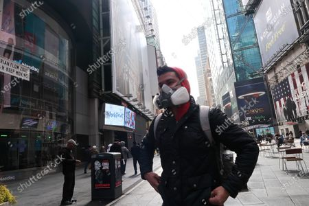 Stock Photo of A man wearing a protective mask walks around the Broadway Theatre that Broadway productions have been suspended on March 12, 2020 in New York City. Amid the COVID19 (coronavirus) concerns and a ban on groups of 500 of people, a directive issued by New York State Andrew Cuomo, all of Broadway performances have been closed until April 12, 2020. President Charlotte St. Martin of the Broadway League issued statement stating that Broadway is committed to enrich and foster enrichment and to inspire all the while entertain its visitors. Additionally, the league is committed to protect all those who work in the industry.