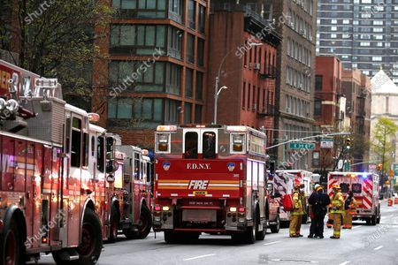 Stock Image of Emergency Services Rescue Personnel and Firemen  in New York, on April 23, 2020. New York Fire Department and Emergency services technicians were dispatched to a high-rise in New York City on April 23, 2020. Scores of firetrucks, ambulances and EMT rescue medics stood ready in front of Murray Hill towers on 2nd Avenue.
