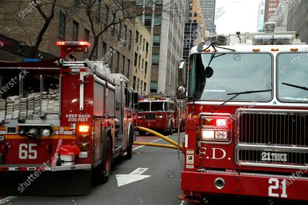 Fire truck stand at the ready  in New York, on April 23, 2020. New York Fire Department and Emergency services technicians were dispatched to a high-rise in New York City on April 23, 2020. Scores of firetrucks, ambulances and EMT rescue medics stood ready in front of Murray Hill towers on 2nd Avenue.