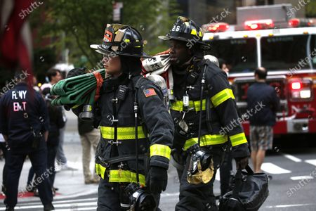 Stock Picture of Firemen carry fire equipment   in New York, on April 23, 2020. New York Fire Department and Emergency services technicians were dispatched to a high-rise in New York City on April 23, 2020. Scores of firetrucks, ambulances and EMT rescue medics stood ready in front of Murray Hill towers on 2nd Avenue.