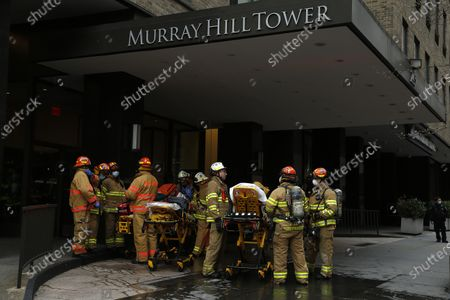 Stock Photo of Emergency Services Rescue Personnel  in New York, on April 23, 2020. New York Fire Department and Emergency services technicians were dispatched to a high-rise in New York City on April 23, 2020. Scores of firetrucks, ambulances and EMT rescue medics stood ready in front of Murray Hill towers on 2nd Avenue.