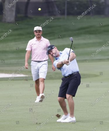 Rory Sabbatini of Slovakia chips in front of Rickie Fowler of the US (L) on the fifth hole during a practice round for the Arnold Palmer Invitational presented by Mastercard golf tournament at the Bay Hill Club & Lodge in Orlando, Florida, USA, 02 March 2021.