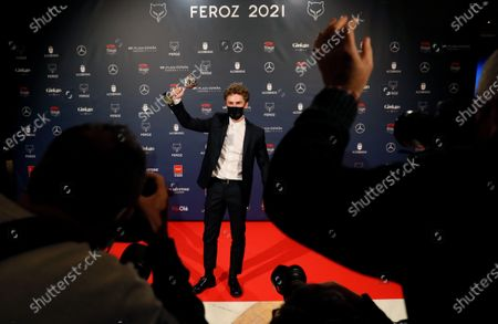 Patrick Criado (C) poses with his trophy after receiving the 'Best Supporting Actor in a TV Series' award during the 8th Feroz Awards gala at the Coliseum Theater in Madrid, Spain, 02 March 2021. The award handout ceremony acknowledges prominent works in Spanish cinema and television productions.