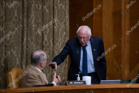 United States Senator Bernie Sanders (Independent of Vermont), Chairman, US Senate Committee on the Budget, right, chats with United States Senator Chuck Grassley (Republican of Iowa) during a Senate Committee on the Budget hearing to examine the nomination of Shalanda D. Young, of Louisiana, to be Deputy Director of the Office of Management and Budget, in the Dirksen Senate Office Building in Washington, DC,.