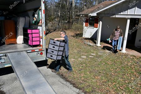 Tanner Ryles, center, and Ray Smith help move the furniture from their friend Kelly Sparrow's home as the Kentucky River inches closer in Frankfort, Ky