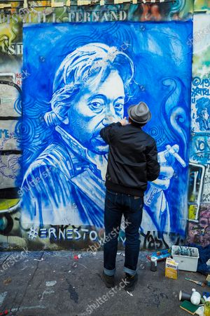 French street artist Ernesto Novo displays his artwork depicting the portrait of singer Serge Gainsbourg on the wall of his home on the occasion of the 30th anniversary of the artist's death on March 02, 2021 in Paris, France. The singer and poet Serge Gainsbourg died on March 02, 1991, his daughter Charlotte Gainsbourg will open her house on rue de Verneuil to the public this year, which will make it a museum and a real place of pilgrimage for her fans.
