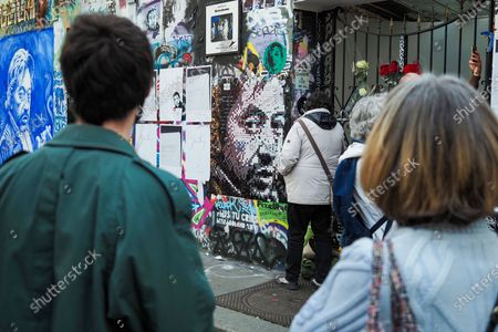 Pedestrians stand in front of the house of French singer Serge Gainsbourg covered with graffitis at the Rue de Verneuil in Paris, on March 2, 2021, 30 years after his death. The singer and poet Serge Gainsbourg died on March 02, 1991, his daughter Charlotte Gainsbourg will open her house on rue de Verneuil to the public this year, which will make it a museum and a real place of pilgrimage for her fans.