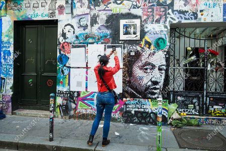Stock Photo of Pedestrians stand in front of the house of French singer Serge Gainsbourg covered with graffitis at the Rue de Verneuil in Paris, on March 2, 2021, 30 years after his death. The singer and poet Serge Gainsbourg died on March 02, 1991, his daughter Charlotte Gainsbourg will open her house on rue de Verneuil to the public this year, which will make it a museum and a real place of pilgrimage for her fans.