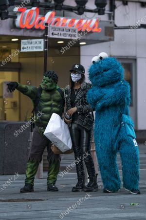 A tourist stops to take a photo with The Hulk and Cookie Monster characters while wearing a PPE mask in Times Square, Manhattan,New York. Mandatory credit: Kostas Lymperopoulos/CSM