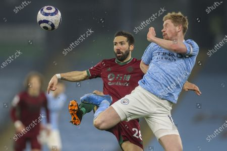 Manchester City's Kevin De Bruyne, right, duels for the ball with Wolverhampton Wanderers' Joao Moutinho during the English Premier League soccer match between Manchester City and Wolves at the Etihad stadium in Manchester, England