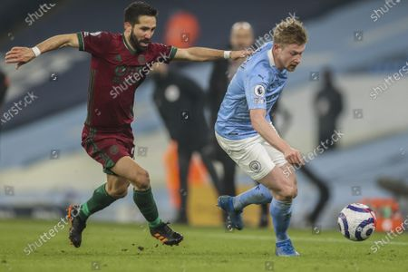 Wolverhampton Wanderers' Ki-Jana Hoever, left, duels for the ball with Manchester City's Kevin De Bruyne during the English Premier League soccer match between Manchester City and Wolves at the Etihad stadium in Manchester, England