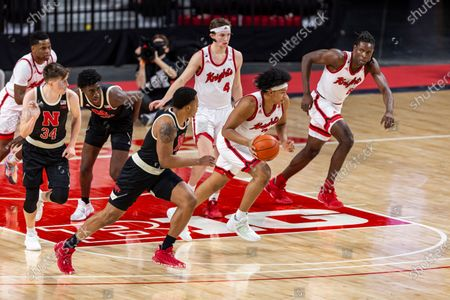 Rutgers guard Ron Harper Jr. (24) dribble the ball against Nebraska guard Shamiel Stevenson (4), foreground in the first half during an NCAA college basketball game, in Lincoln, Neb