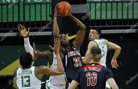 Arizona center Christian Koloko (35) hauls in a rebound over Oregon forward Chandler Lawson (13) and Oregon guard Chris Duarte (5) during the second half of an NCAA college basketball game, in Eugene, Ore