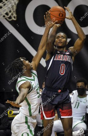 Arizona guard Bennedict Mathurin (0) shoots over Oregon forward Eric Williams Jr. (50) during the first half of an NCAA college basketball game, in Eugene, Ore