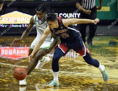 Oregon forward Eric Williams Jr. (50) and Arizona guard Kerr Kriisa (25) battle for a loose ball during the first half of an NCAA college basketball game, in Eugene, Ore