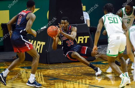 Arizona center Christian Koloko (35) passes the ball to Arizona guard Bennedict Mathurin (0) as Oregon forward Eric Williams Jr. (50) and Oregon forward Eugene Omoruyi (2) defend on the play during the first half of an NCAA college basketball game, in Eugene, Ore