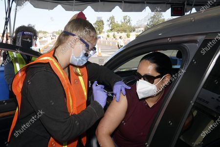 Stock Photo of Vanessa Guerra, at right, a special education teacher at Grant Elementary School in Hollywood, receives a shot of the Moderna COVID-19 vaccine from nurse Kelly Mendoza at a site for employees of the Los Angeles school district in the parking lot of SOFI Stadium, in Inglewood, Calif