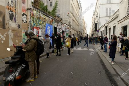 The crowd pays tribute to the singer Serge Gainsbourg in front his home in Paris, Rue de Verneuil, on March 2, 2021. Street artist Ernesto Novo paints a fresca of the artist