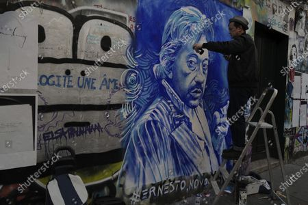 """French street artist Ernesto Novo paints a portrait to pay tribute to late French musician, song writer and singer Serge Gainsbourg on the wall outside his house in Paris, France, . Three decades after his death, Gainsbourg's music has reached legendary stature in France, and he has also gained a cult following in the English-speaking world with chart success in the United Kingdom and the United States with """"Je t'aime... moi non plus"""" and """"Bonnie and Clyde"""", respectively"""