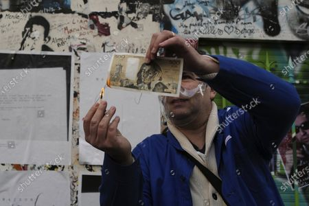 """Man burns a copy of a 500 Francs note as a tribute to late French musician, song writer and singer Serge Gainsbourg outside his house in Paris, France, . Three decades after his death, Gainsbourg's music has reached legendary stature in France, and he has also gained a cult following in the English-speaking world with chart success in the United Kingdom and the United States with """"Je t'aime... moi non plus"""" and """"Bonnie and Clyde"""", respectively"""