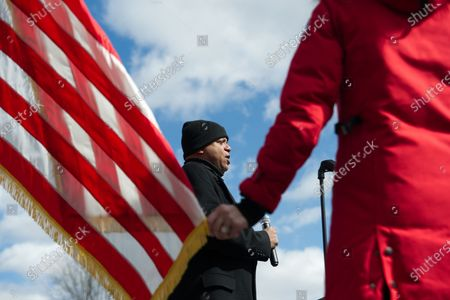 Stock Photo of At the start of a pro-trump rally as the National Anthem is performed MC Erin Elmore holds a tip of the American flag, in Bensalem, PA, on March 4th, 2017.