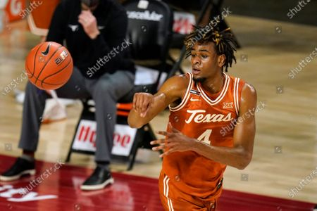 Texas forward Greg Brown passes the ball during the first half of an NCAA college basketball game against Iowa State, in Ames, Iowa