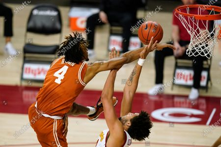 Texas forward Greg Brown (4) passes over Iowa State forward George Conditt IV, right, during the first half of an NCAA college basketball game, in Ames, Iowa