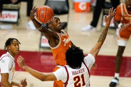 Texas guard Andrew Jones drives to the basket over Iowa State guard Jaden Walker (21) during the first half of an NCAA college basketball game, in Ames, Iowa